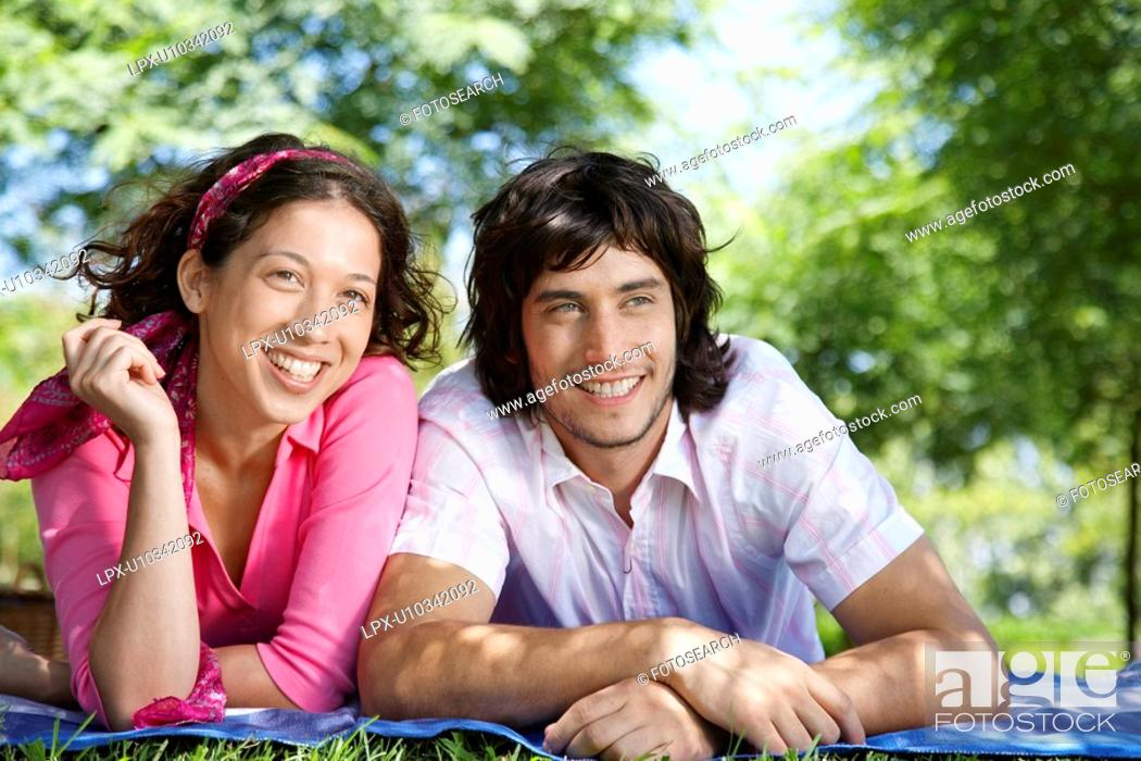 Stock Photo: Young couple lying on blanket in park.
