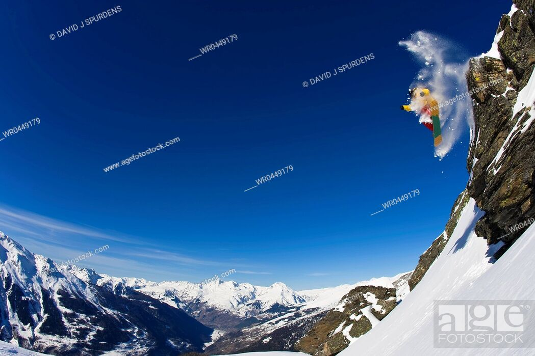 Stock Photo: Snowboarding drops while spinning of a cliff enveloped in fresh powder snow.