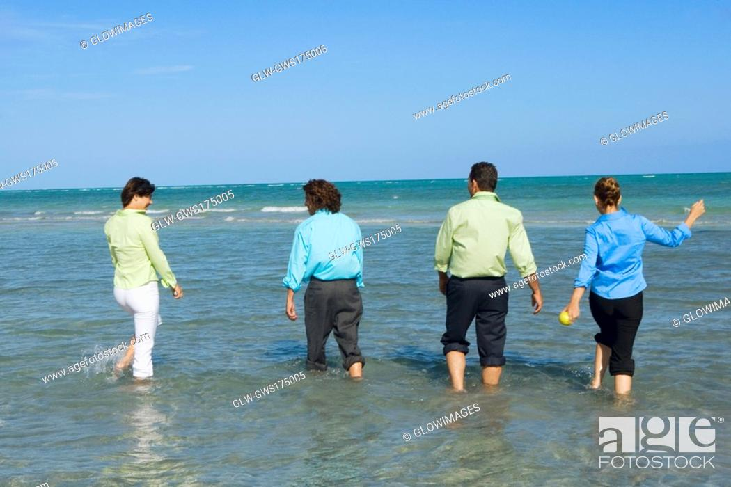 Stock Photo: Rear view of two mid adult couples wading on the beach.