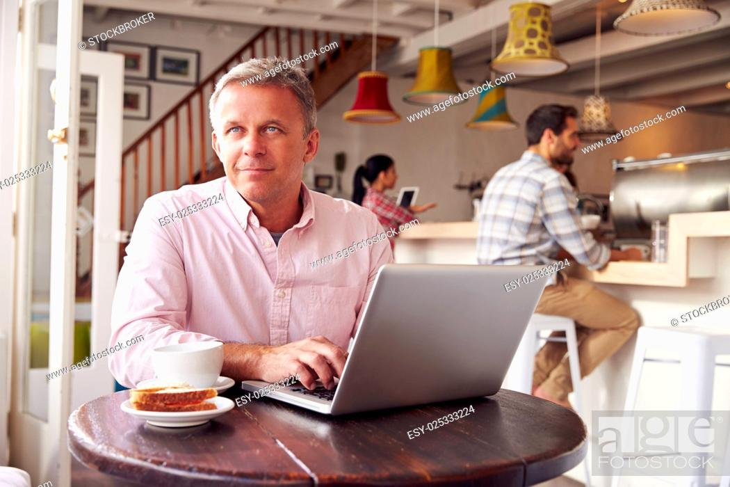 Stock Photo: Middle aged man using laptop in a cafe.