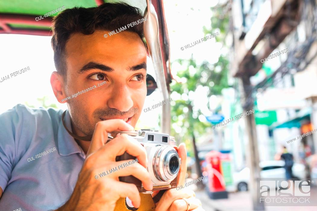 Stock Photo: Young male tourist in auto rickshaw with camera, Bangkok, Thailand.