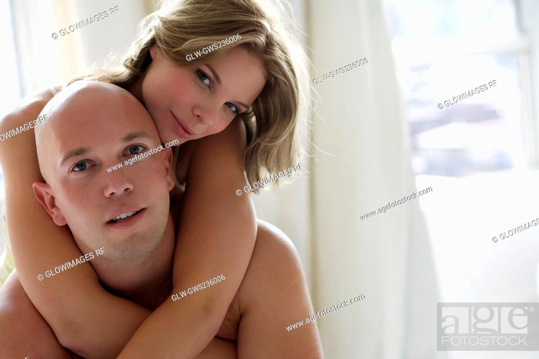 Stock Photo: Portrait of a young woman embracing a young man from behind.