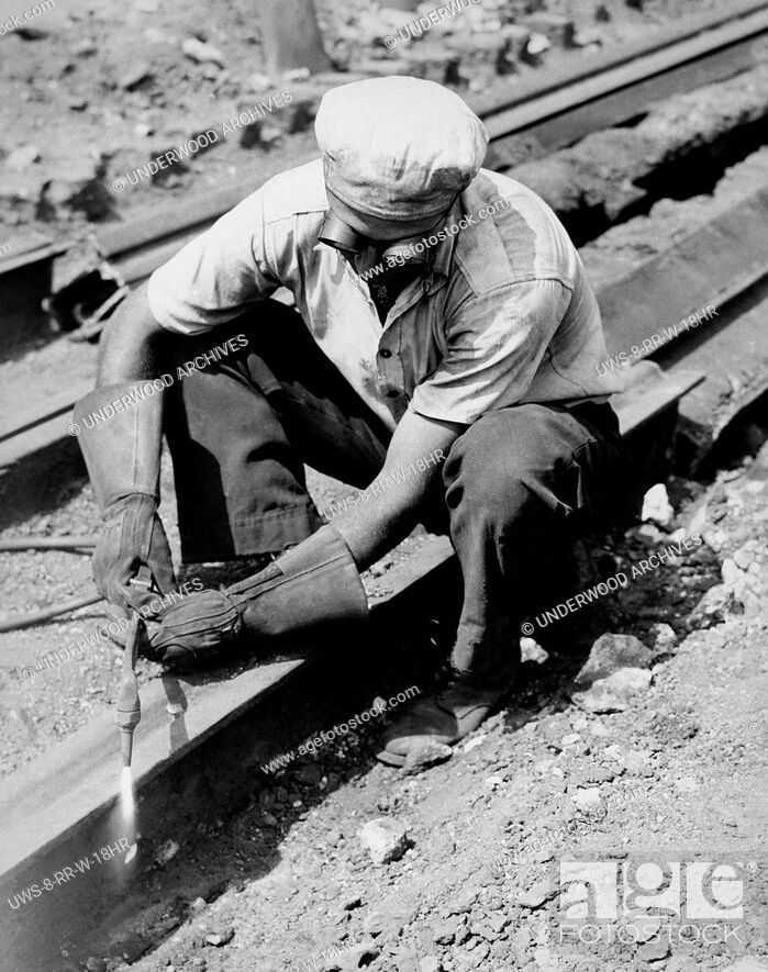 Stock Photo: United States: c. 1935 A man working at dismantling railroad tracks by cutting them with a torch.