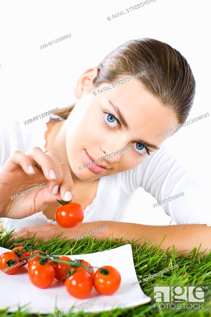 Stock Photo: young woman eating tomatoes.