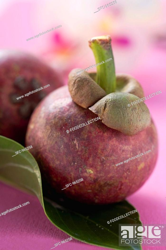Stock Photo: Two mangosteens with leaf.