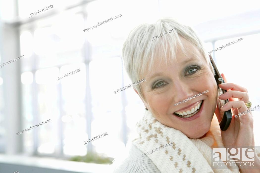 Stock Photo: Happy mature woman on the phone at airport.