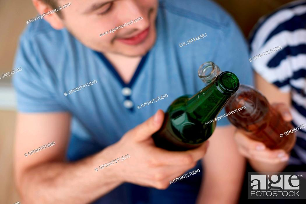 Photo de stock: Young couple sitting outdoors, toasting with bottled beers.
