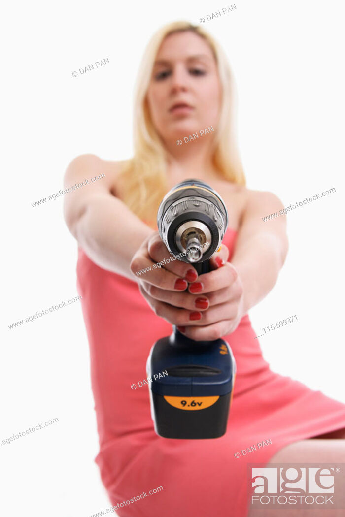 Stock Photo: Young girl in her 20's holding a power tool/ drill in her hand pointing to the camera.