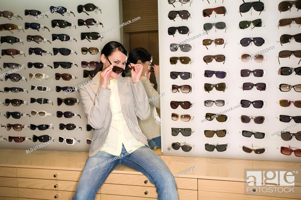 Stock Photo: Woman posing in front of sunglasses display.