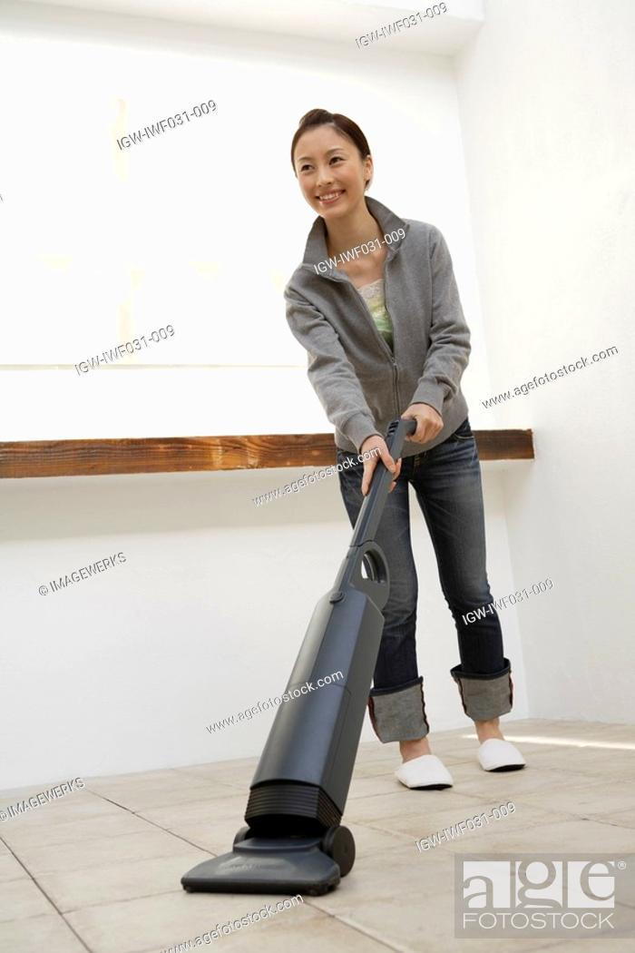 Stock Photo: View of a young woman cleaning floor with a vacuum cleaner.