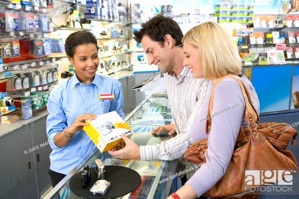Stock Photo: Young couple with saleswoman, looking at camera, smiling, side view.