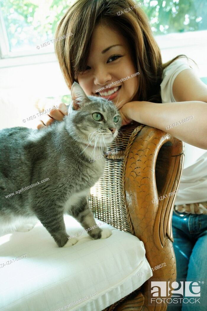 Imagen: Close-up of a young woman playing with a cat.
