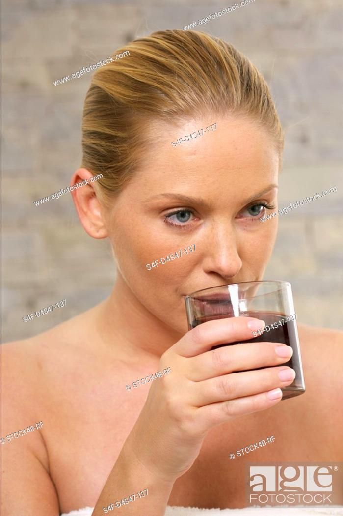 Stock Photo: Young woman drinking glass of juice.