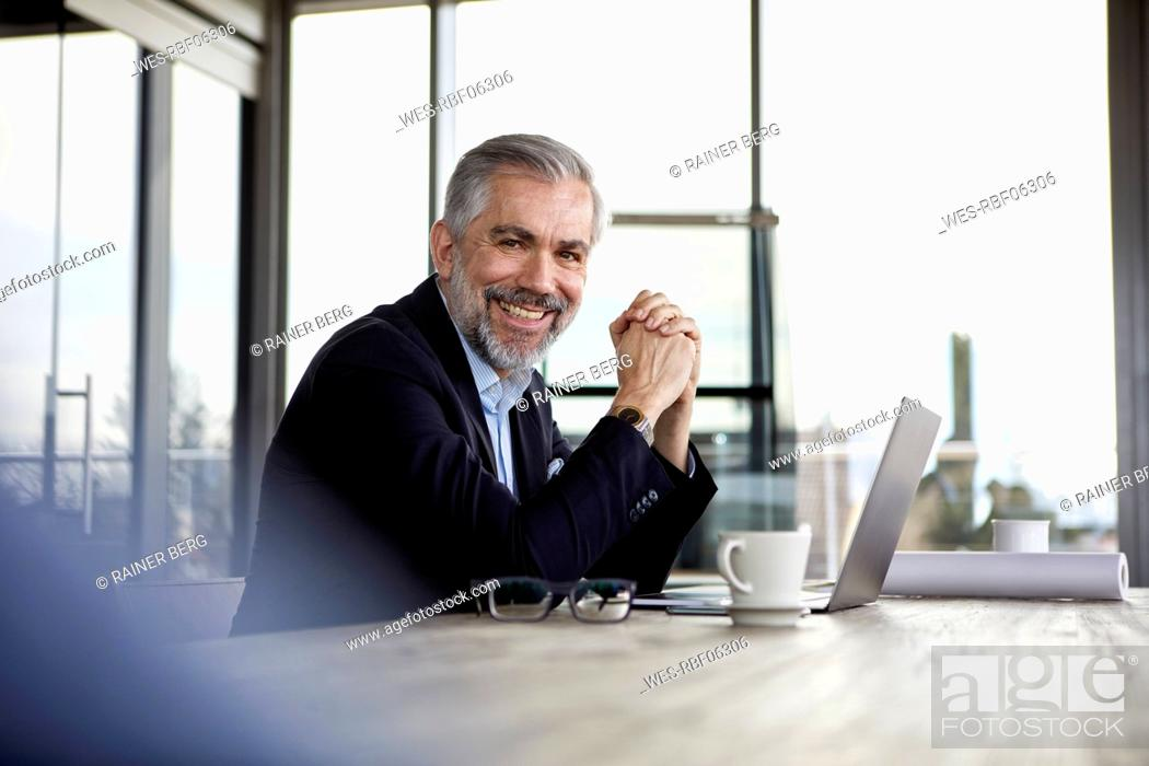 Stock Photo: Portrait of smiling businessman with laptop at desk in office.