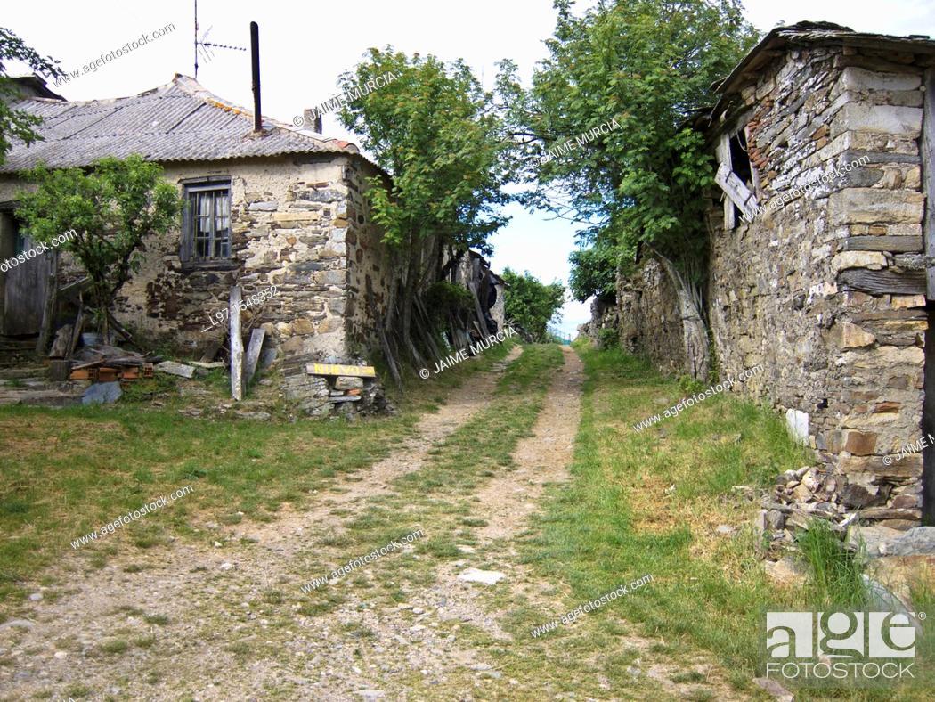 Stock Photo: Gravel road between two stone buildings in the village of Foncebadon along the Camino de Santiago.