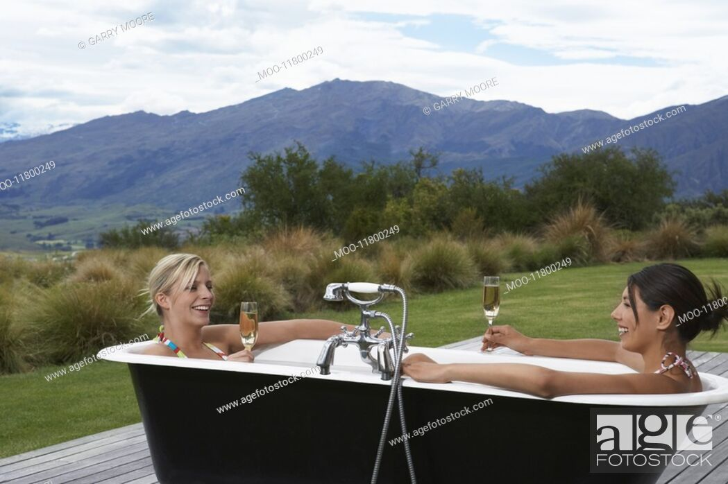 Stock Photo: Two women taking bath with champagne on porch near mountains.