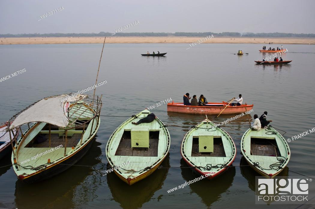 Stock Photo: Boats + tourists boating on the Ganges river (Varanasi, India).