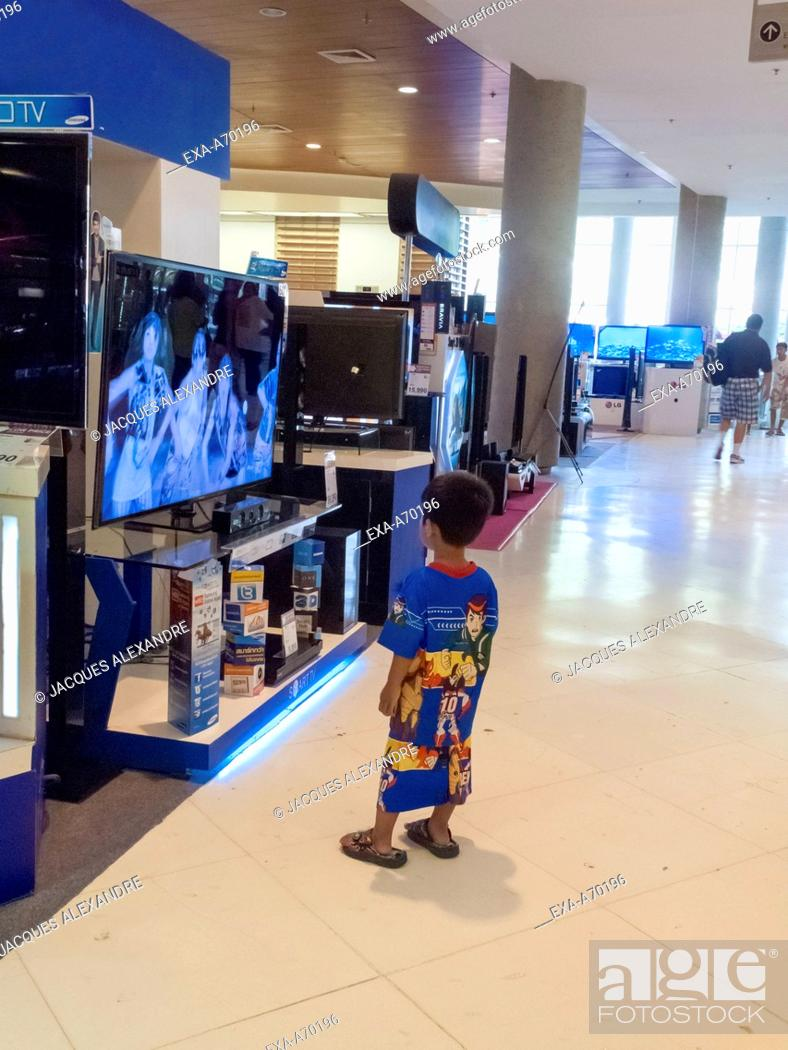 Stock Photo: child fascinated by TV screens.