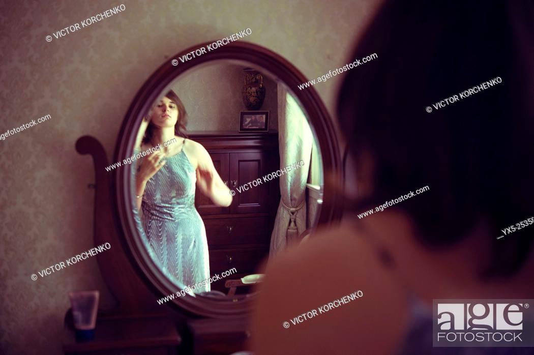Stock Photo: Young woman dressing in front of a vanity mirror.