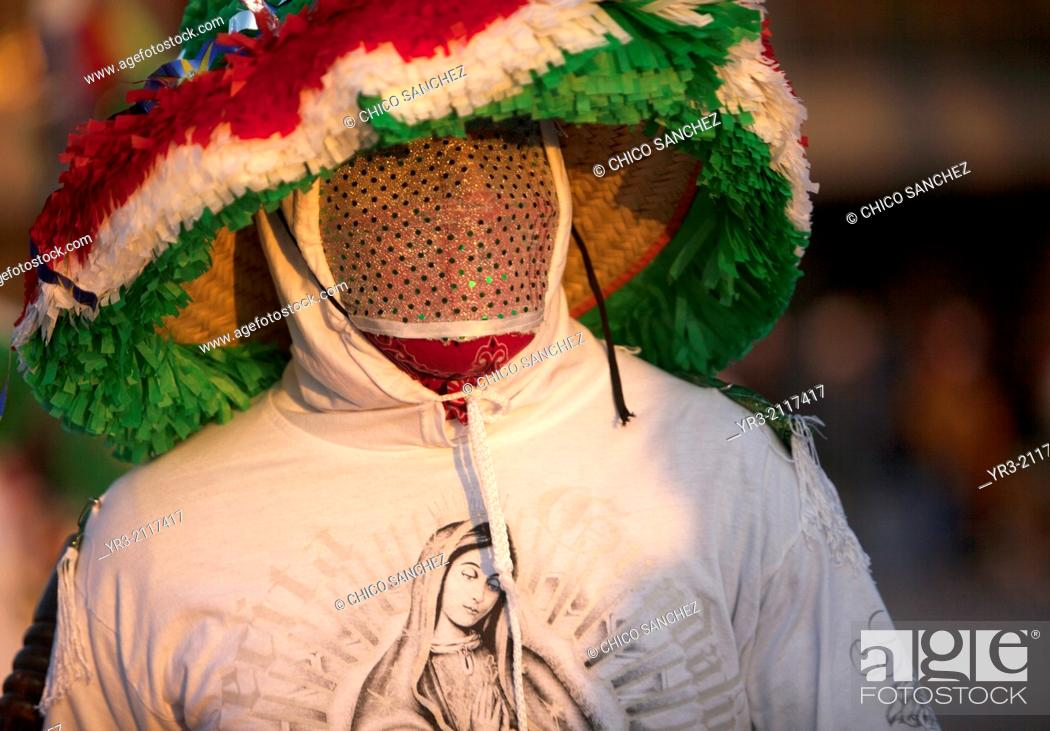 Stock Photo: A dancer from Chocaman, Veracruz, wearing a shirt with the image of Our Lady of Guadalupe and wearing a mask, dances the Danza de los Santiagos at the.