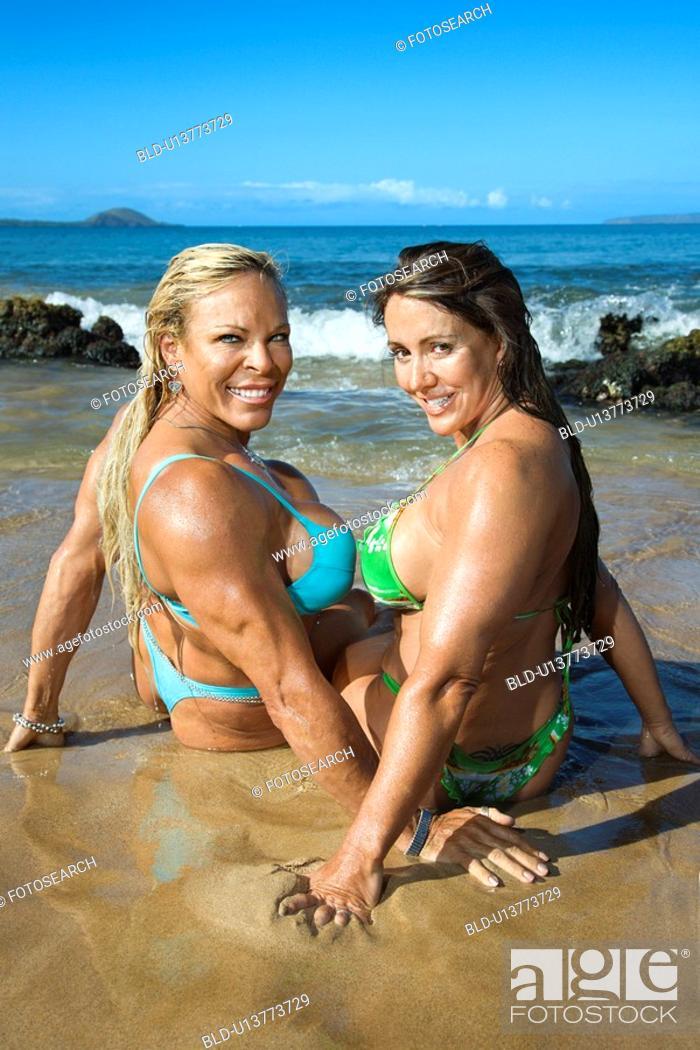 Stock Photo: Women bodybuilders in bikinis sitting in sand on beach.