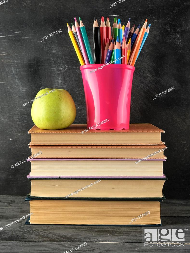 Stock Photo: stack of books and a blue stationery glass with multi-colored wooden pencils, back to school concept.
