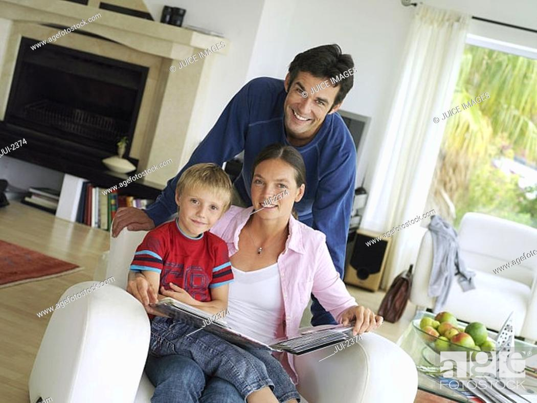 Stock Photo: Family relaxing at home, boy 5-7 in mother's lap in armchair with photo album, portrait tilt.