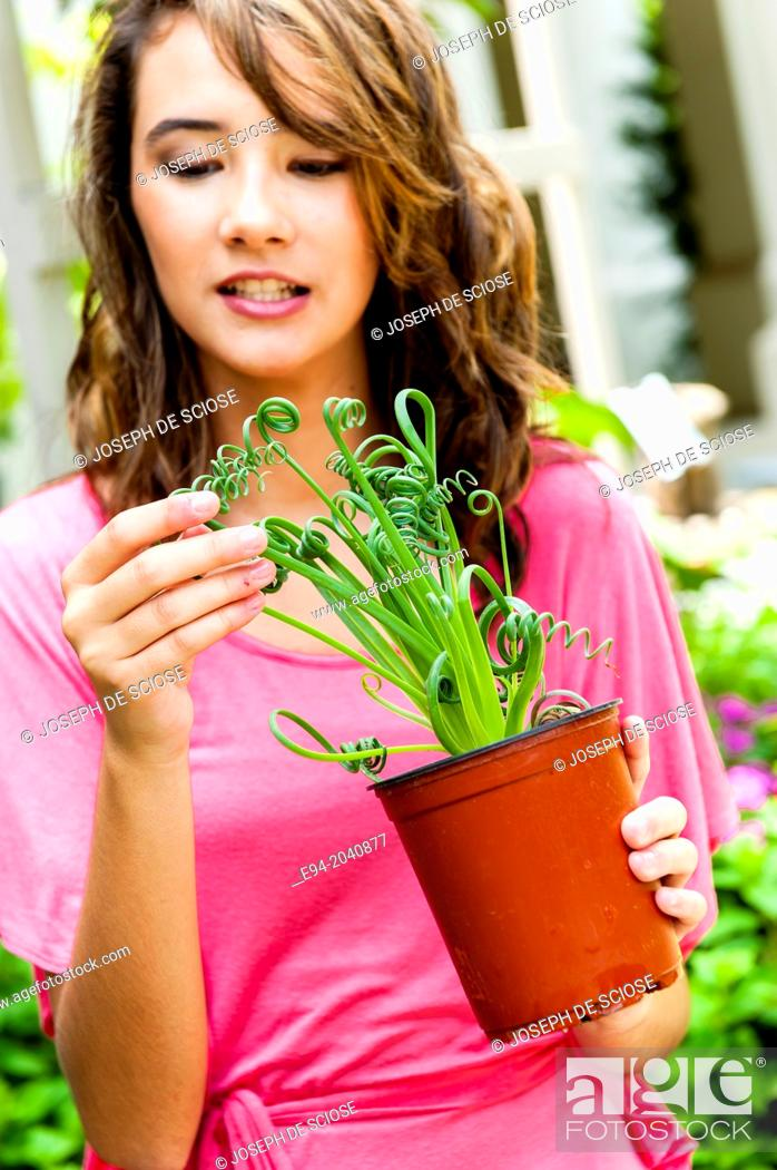 Stock Photo: A smiling 14 year old brunette looking at a plant in plant nursery.