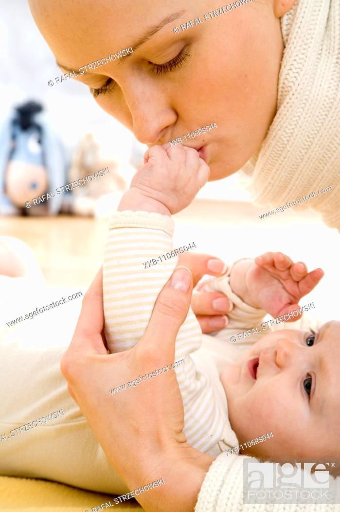Stock Photo: mum kissing baby's hand.