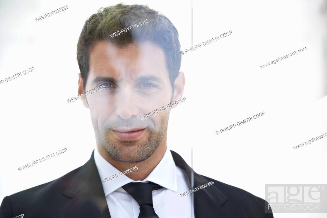Stock Photo: Spain, Businessman standing by door, portrait.
