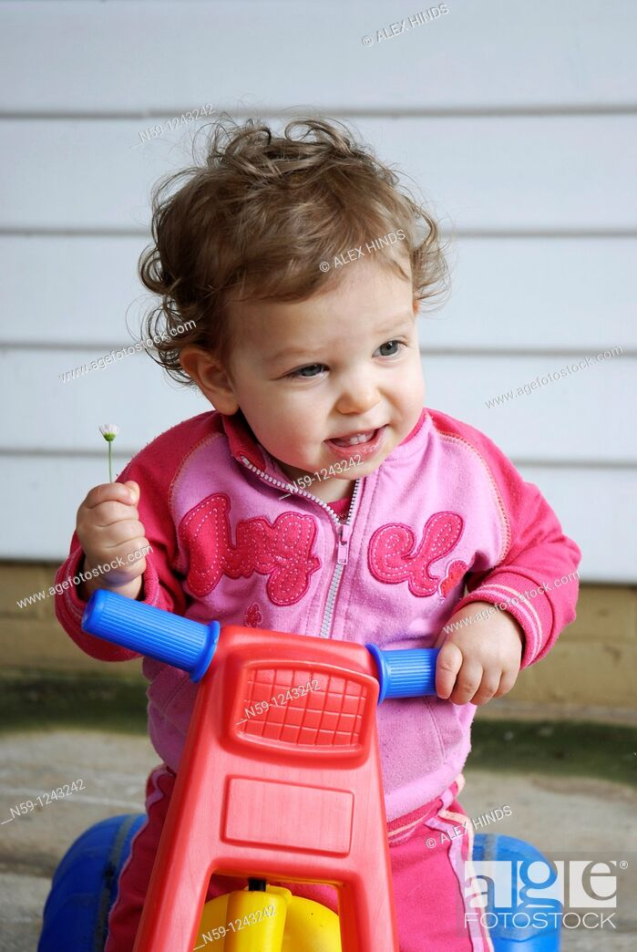 Stock Photo: Toddler girl playing on a plastic tricycle.