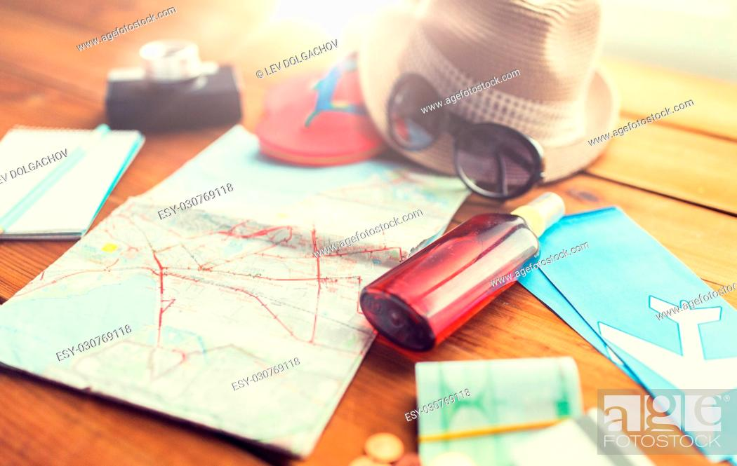 Stock Photo: summer vacation, tourism and objects concept - close up of travel map, airplane tickets, money and personal accessories.