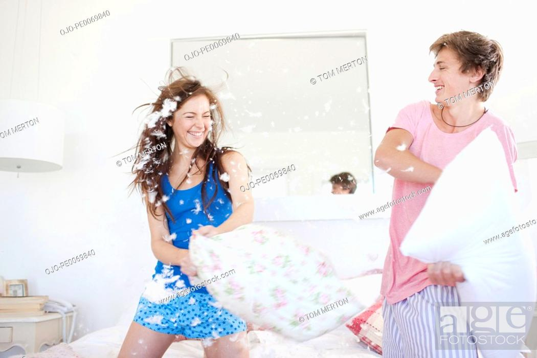 Stock Photo: Couple pillow fighting in bedroom.