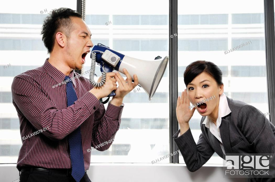 Stock Photo: Businessman yelling through a megaphone at his colleague.