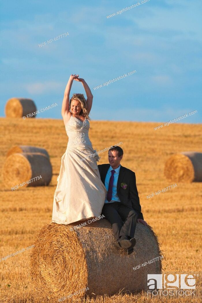 Stock Photo: Newly-wed couple in their wedding clothes in field of hay.