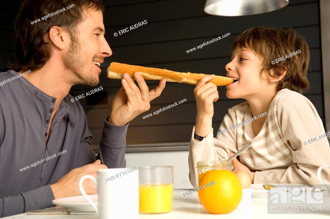 Stock Photo: Mid adult man eating a baguette with his son.