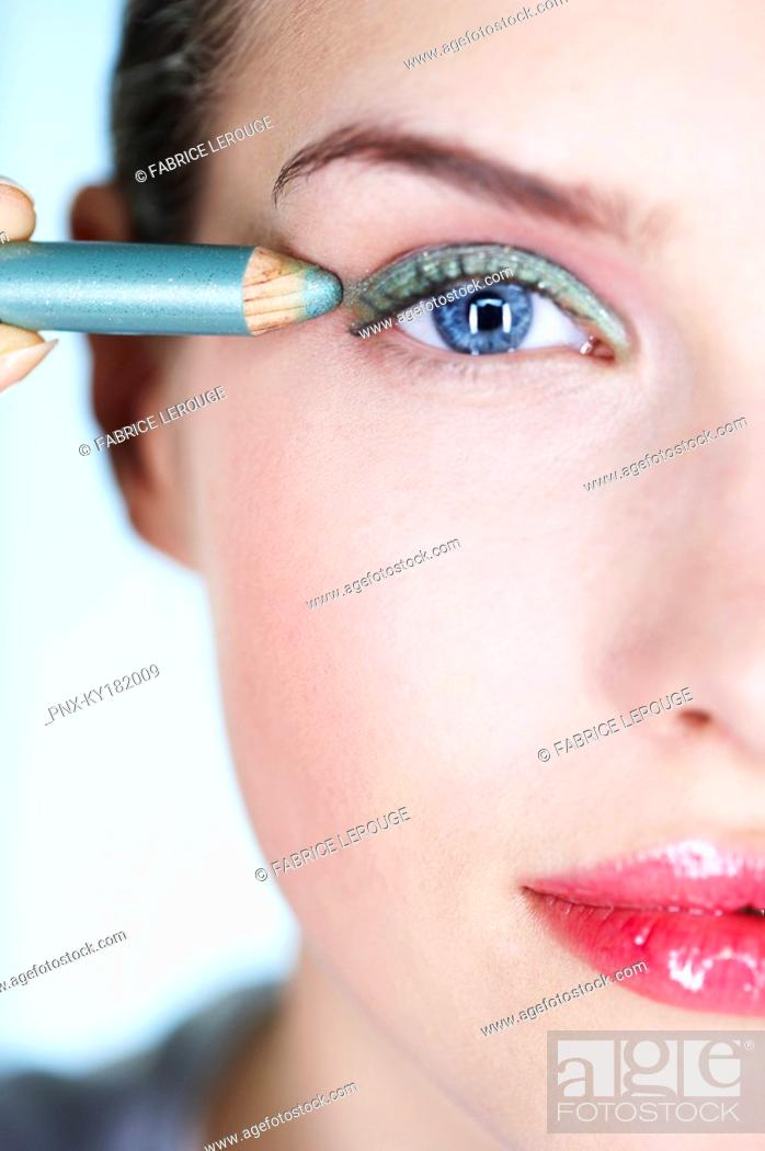 Stock Photo: Young woman applying eyeliner.