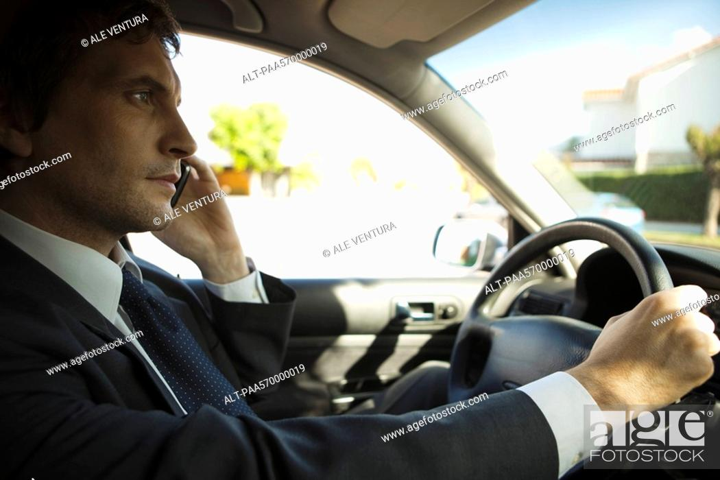 Stock Photo: Businessman using cell phone while driving.
