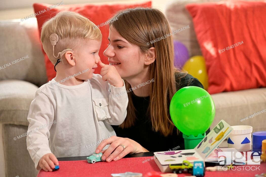 Stock Photo: A Boy With A Hearing Aids And Cochlear Implants Playing.