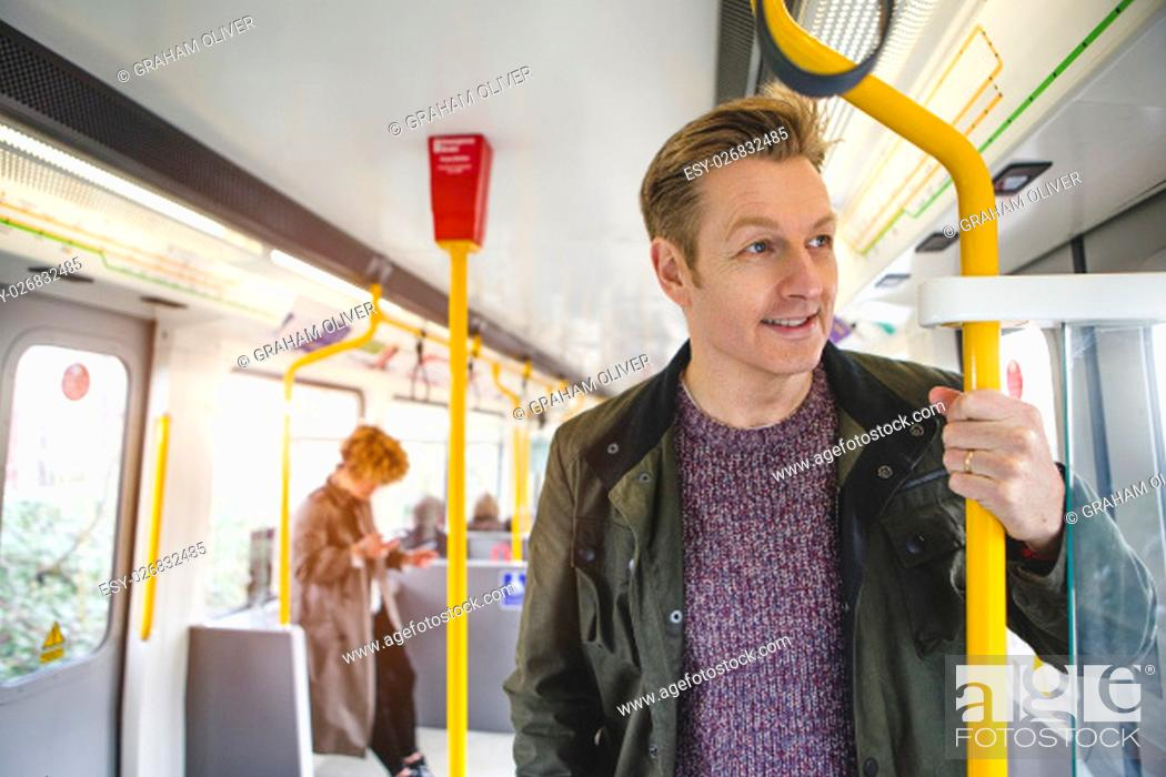 Stock Photo: Man standing on the train holding on to the hand rail. He is looking out the window with a cheerful expression.