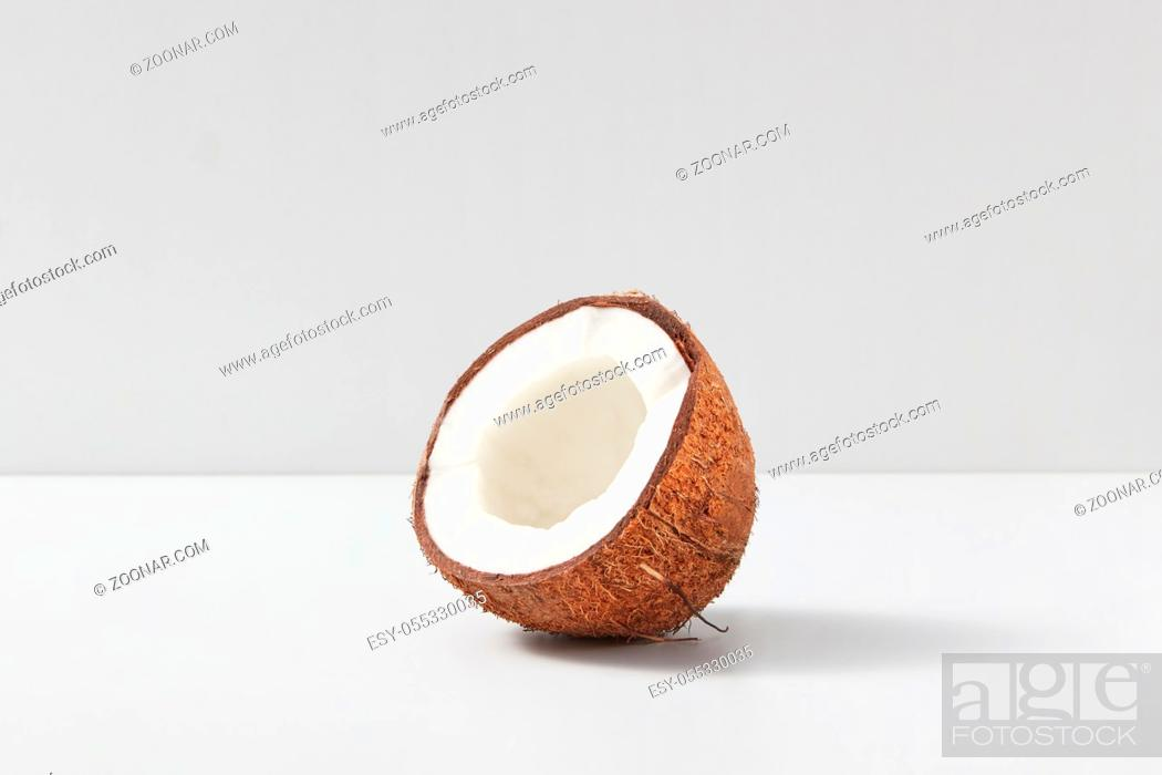 Stock Photo: Natural organic tropical fruit half of ripe coconut on a light grey duotone background, copy space. Vegetarian concept.