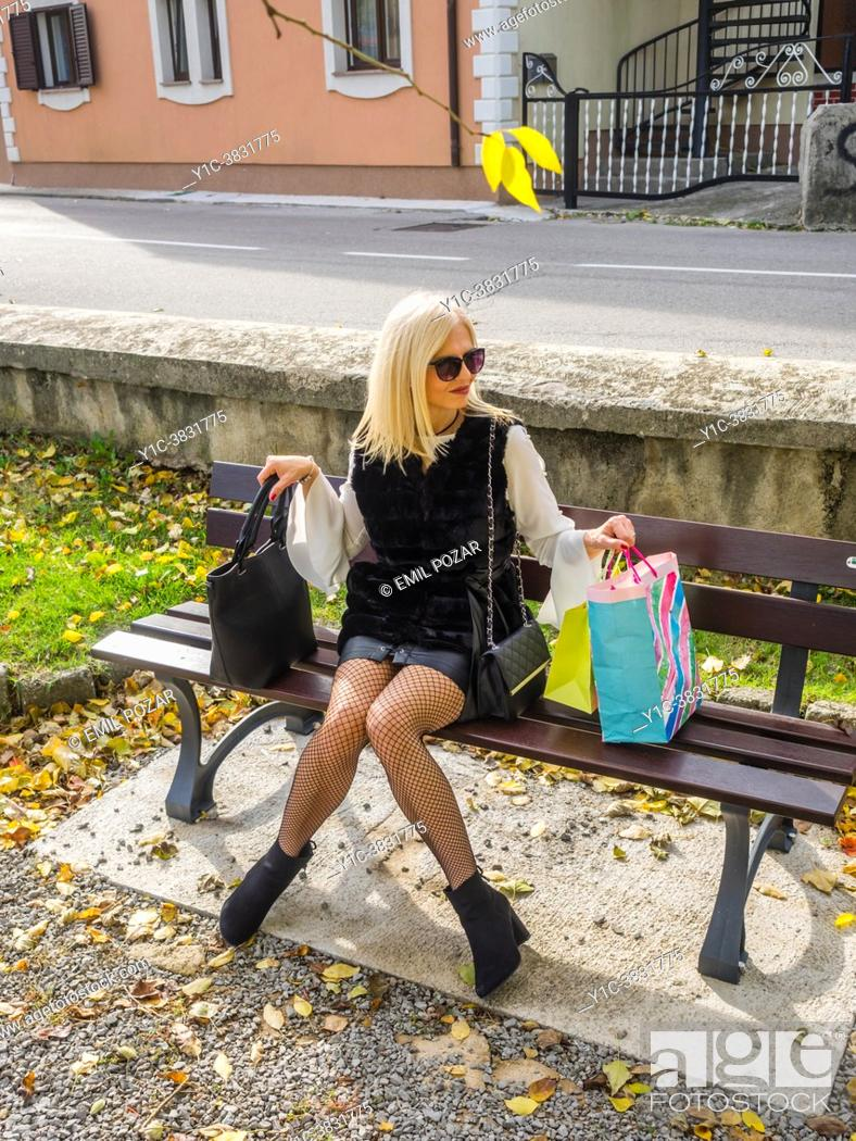 Stock Photo: Attractive mature blonde woman in park after shopping with bags full.