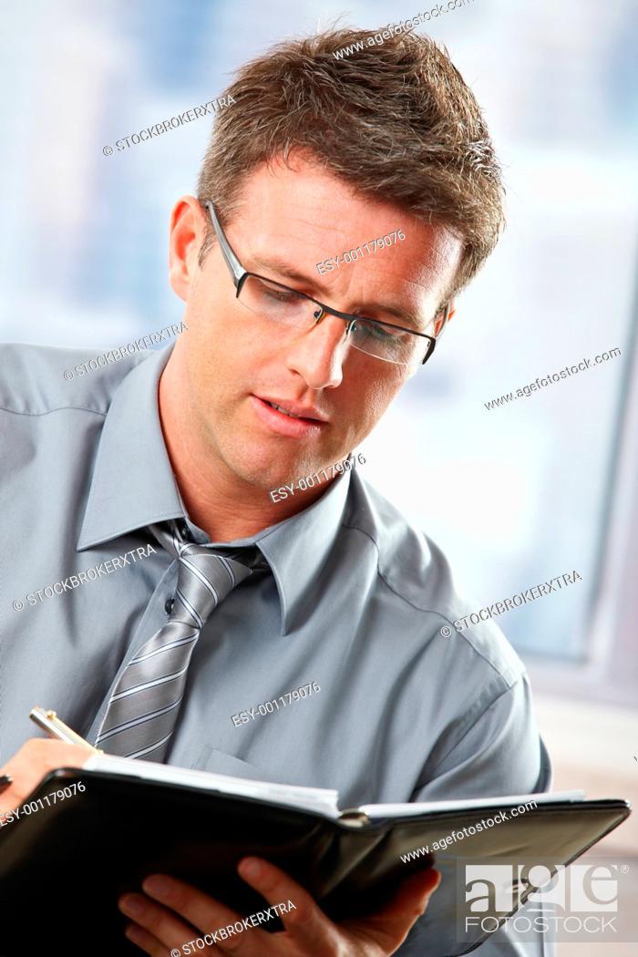 Stock Photo: Businessman taking notes into organiser.
