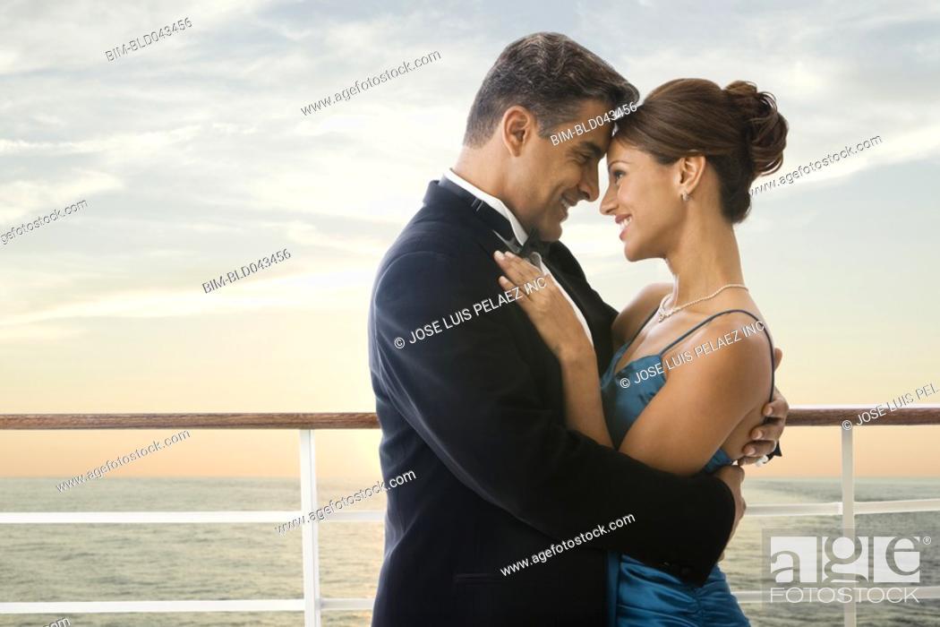 Stock Photo: Hispanic couple in eveningwear on ship.