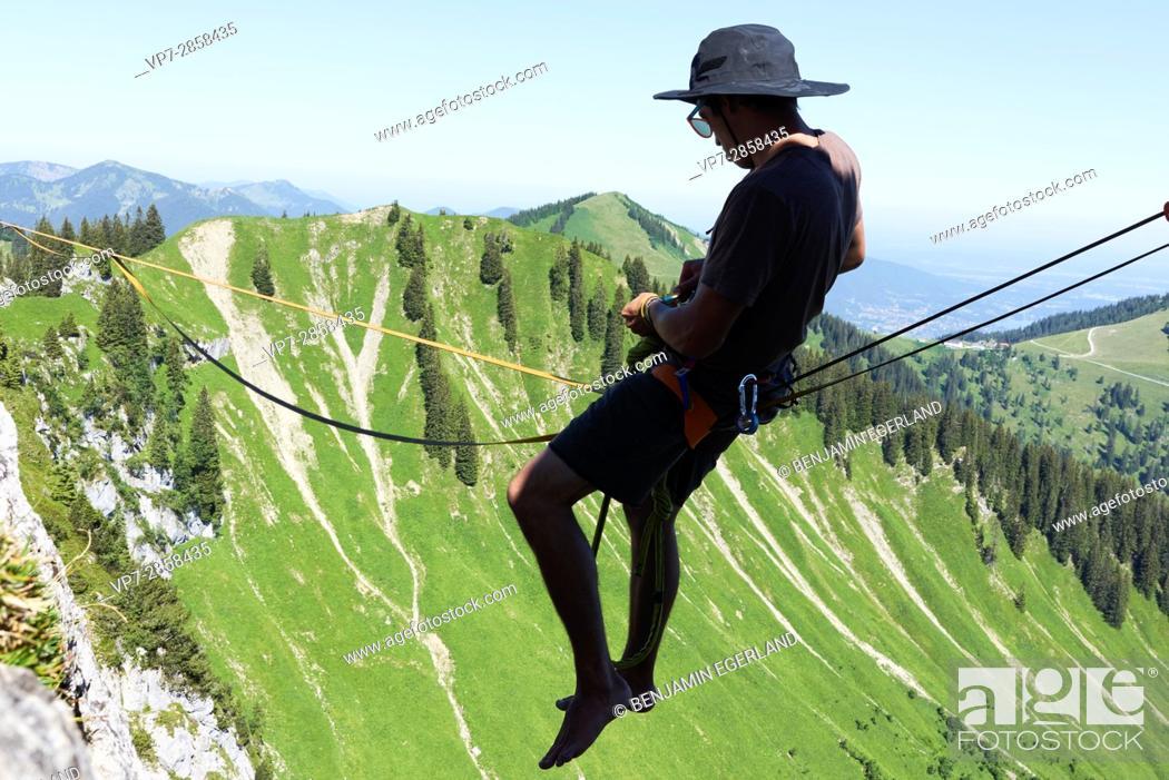 Stock Photo: man sitting on highline in Bavarian alps, near mountain Blankenstein, south of Germany.