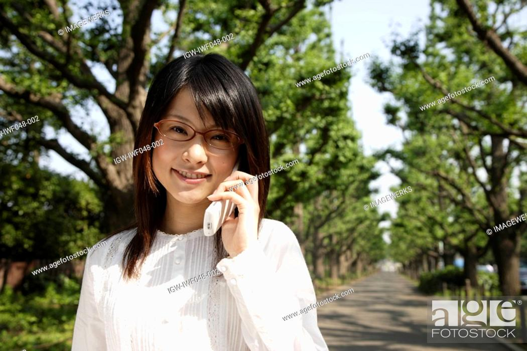 Stock Photo: Portrait of a young woman talking on mobile phone.