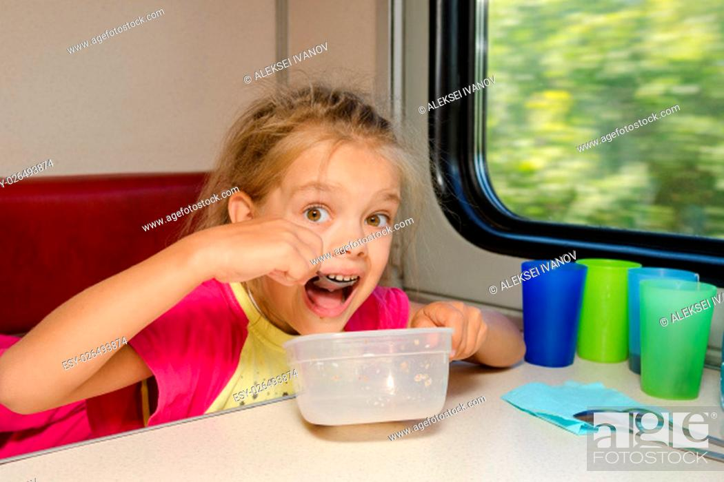 Stock Photo: The girl on the train sits at a table on the lower place in the second-class compartment of the car and eats it with relish spoon.