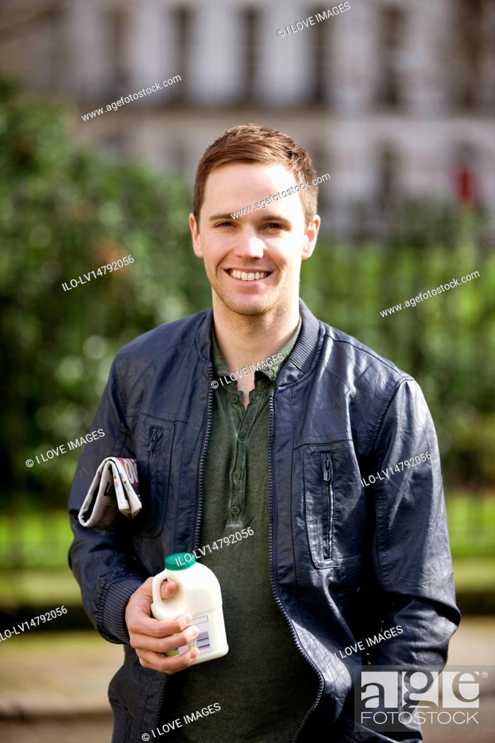Stock Photo: A young man standing outdoors, holding a newspaper and a pint of milk.