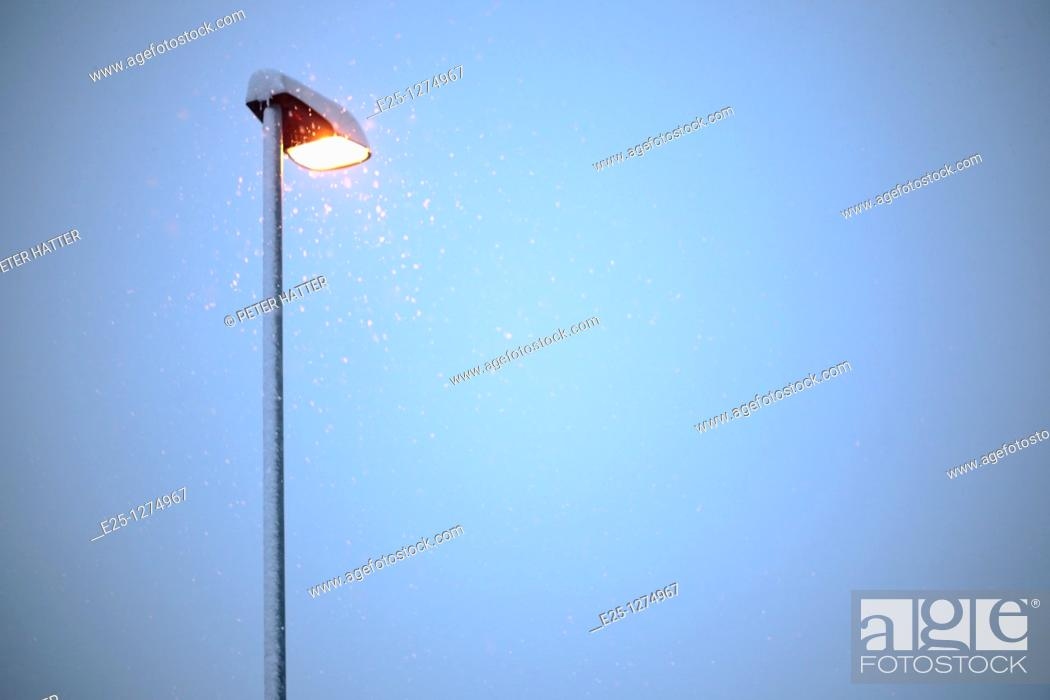 Stock Photo: Snow falls past an illuminated street lamp in winter.