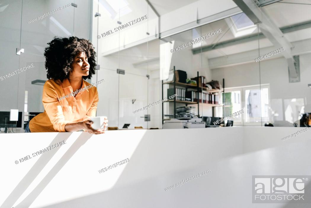 Stock Photo: Young woman having a coffee break in office.